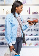 Woman in mall with shopping bags looking at shoes