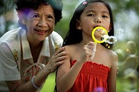 Woman and young girl blowing bubbles