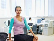 Businesswoman sitting on desk in office with co-workers in background