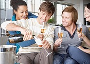 Four friends on sofa with champagne
