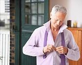 Man in bedroom getting dressed for work