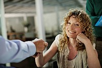 Woman shaking businessman´s hand with man in background