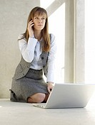 Woman with a laptop is phoning