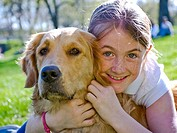 Young girl hugging her one year old golden retriever in central park, USA