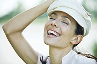 Woman holding hat on head, laughing, close-up