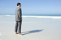 Businessman standing barefoot on beach, looking at view