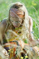 Young woman crouching to pick flowers in field, close-up