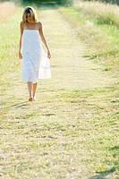 Young woman walking barefoot along rural path