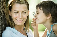 Mother and son, boy looking through magnifying glass, close-up