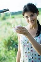 Young woman rinsing off bowl of cherry tomatoes, smiling at camera