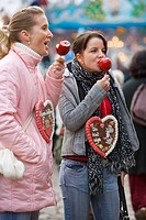 Two girls eating glaced apples at the Bremen Annual Fair in Germany, Europe