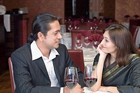 Mid adult man with a young woman looking at each other and sitting in a restaurant