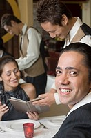 Portrait of a mid adult man smiling and a waiter taking order from a young woman in a restaurant