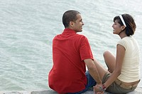 Young couple sitting on the ledge and looking at each other