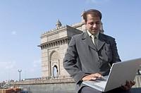 Businessman using a laptop with a monument in the background, Gateway of India, Mumbai, Maharashtra, India
