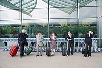 Three businesswomen with two businessmen waiting at an airport lounge