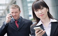 Close-up of a businesswoman holding a personal data assistant with a businessman talking on a mobile phone behind her