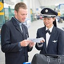Businessman showing an airplane ticket to a female pilot