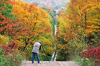a photographer and autumn foliage on burnette´s side road, manitoulin island, ontario, Canada