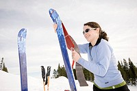 A woman attaches her climbing skins to her backcountry skis in preparation for climbing up the hill for another run  Strathcona Provincial Park, Briti...