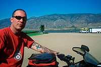 Motorcycle rider at beach in Osoyoos, British Columbia, Canada