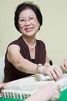Portrait of a senior woman playing mahjong