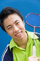 Portrait of a young man holding a badminton racket and smiling