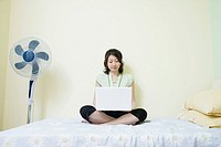 Young woman sitting cross-legged on the bed and using a laptop