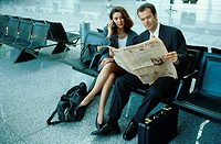 Couple in Airport on Phone with Paper