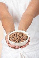 Bowl of almonds in woman's hands