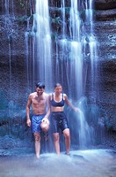Man and Woman Standing Under a Waterfall