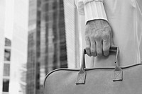 Mid section view of a businessman holding a handbag