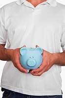 Mid section view of a person holding a piggy bank