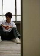 Man sitting by window in school uniform