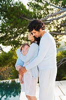 Family w/ baby embracing in nature