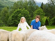 Young boy and young girl smiling and feeding sheep in a field