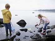 Young boy and young girl on large rocks fishing in a lake with nets