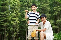 Father and son playing baseball in the park