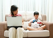 Mother using laptop while looking at son playing toy cars