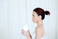 Woman drinking a glass of milk with drinking straw