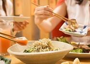 People Having Salad with Chopsticks