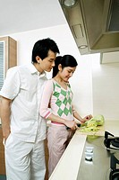 Woman cutting vegetables in the kitchen, man standing by the side