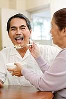 Senior woman feeding senior man cereal