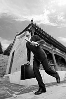 Businessman running while holding baton and briefcase