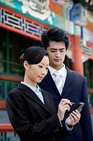 Businesswoman using palmtop, businessman watching