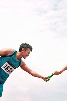 Two men´s hands passing the baton in a relay race