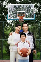 Boy with basketball posing with senior man and woman