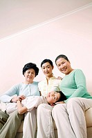 Female generations of a family sitting on couch, boy lying on their laps