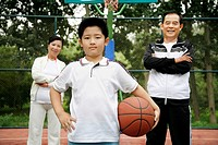 Boy holding basketball, senior man and woman standing behind him