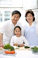 Girl, senior man and woman preparing food in the kitchen